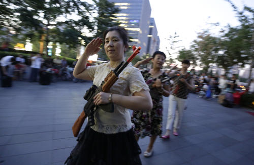"Local women holding toy guns salute before they dance to revolutionary songs as part of their daily exercise at a square outside a shopping mall in Beijing. About 30 local residents formed this ""Nanguan"" art group that enjoys performing and dancing to revolutionary songs as part of their nightly fitness activity."