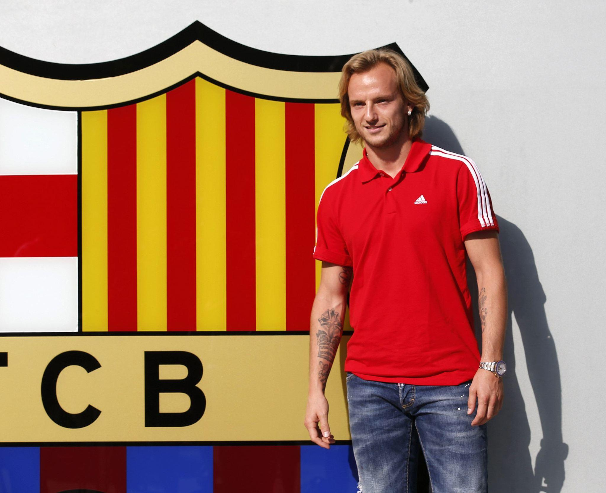 Croatian soccer player Ivan Rakitic poses next to FC Barcelona crest before signing his contract at the club's headquarters in Barcelona June 30, 2014 REUTERS/Gustau Nacarino (SPAIN - Tags: SPORT SOCCER) ORG XMIT: BAR03