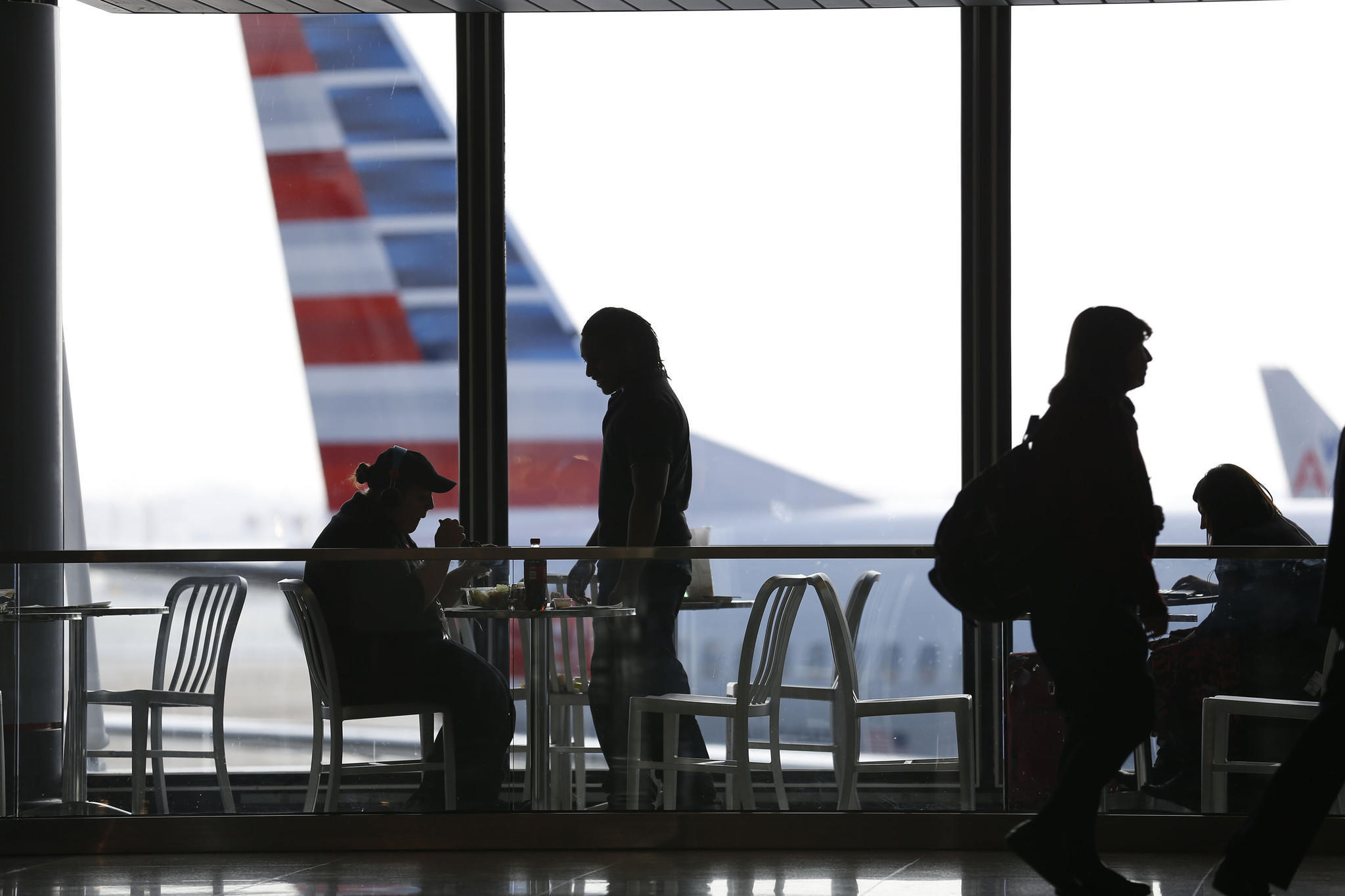 Travelers sit and eat as an American Airlines plane sits in a gate in terminal 3 at Chicago's O'Hare International Airport.