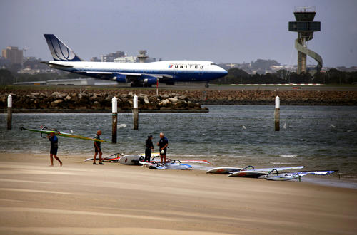 A man carries his sailboard away from fellow windsurfers along a stretch of beach located next to the runway of Sydney's Kingsford Smith International Airport at Botany Bay February 26, 2013.