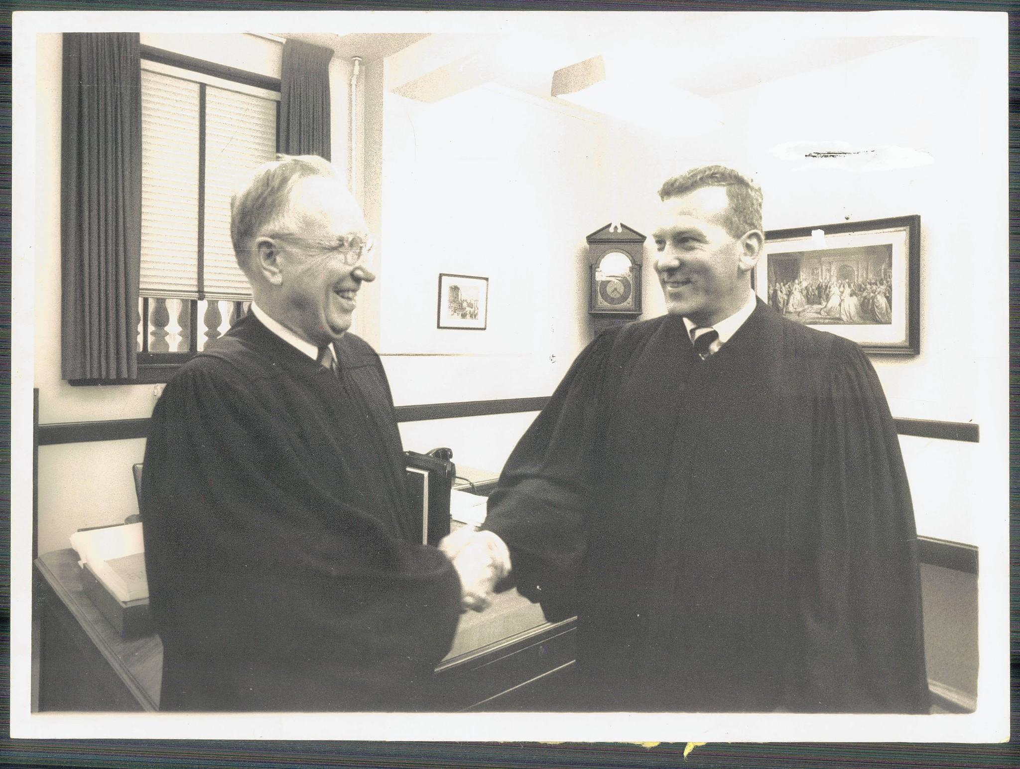 Judge Roszel C Thomsen (left) shakes the hand of Judge James R Miller Jr. after he was sworn in. Judge MIller, who died in June, was a judge in Baltimore for 15 years.