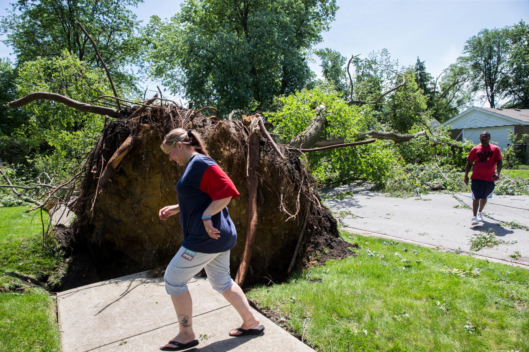 Residents Nicole and Ken Bledsoe walk to their house past a large tree toppled during last night's storms, at 148th Street and Kilbourn, in Midlothian.