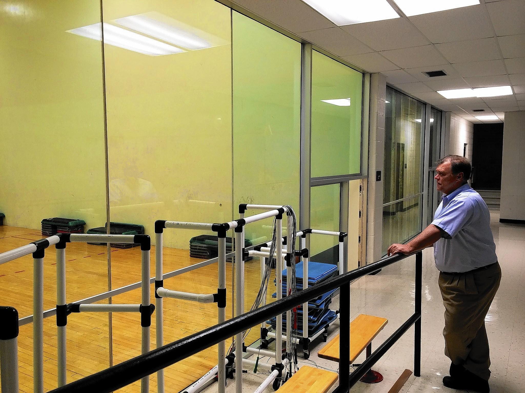 John Baird, assistant superintendent of operations for District 303, looks out at one of three racquetball courts where mold was discovered. The court above is occassionally used as a stretching area, but the other two remain empty.