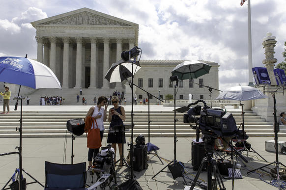 News media crews wait for the Harris vs. Quinn decision in the final days of the Supreme Court's term. The high court held that personal home-care employees cannot be forced to pay dues to a union, but it stopped short of extending the ruling to all public employees.