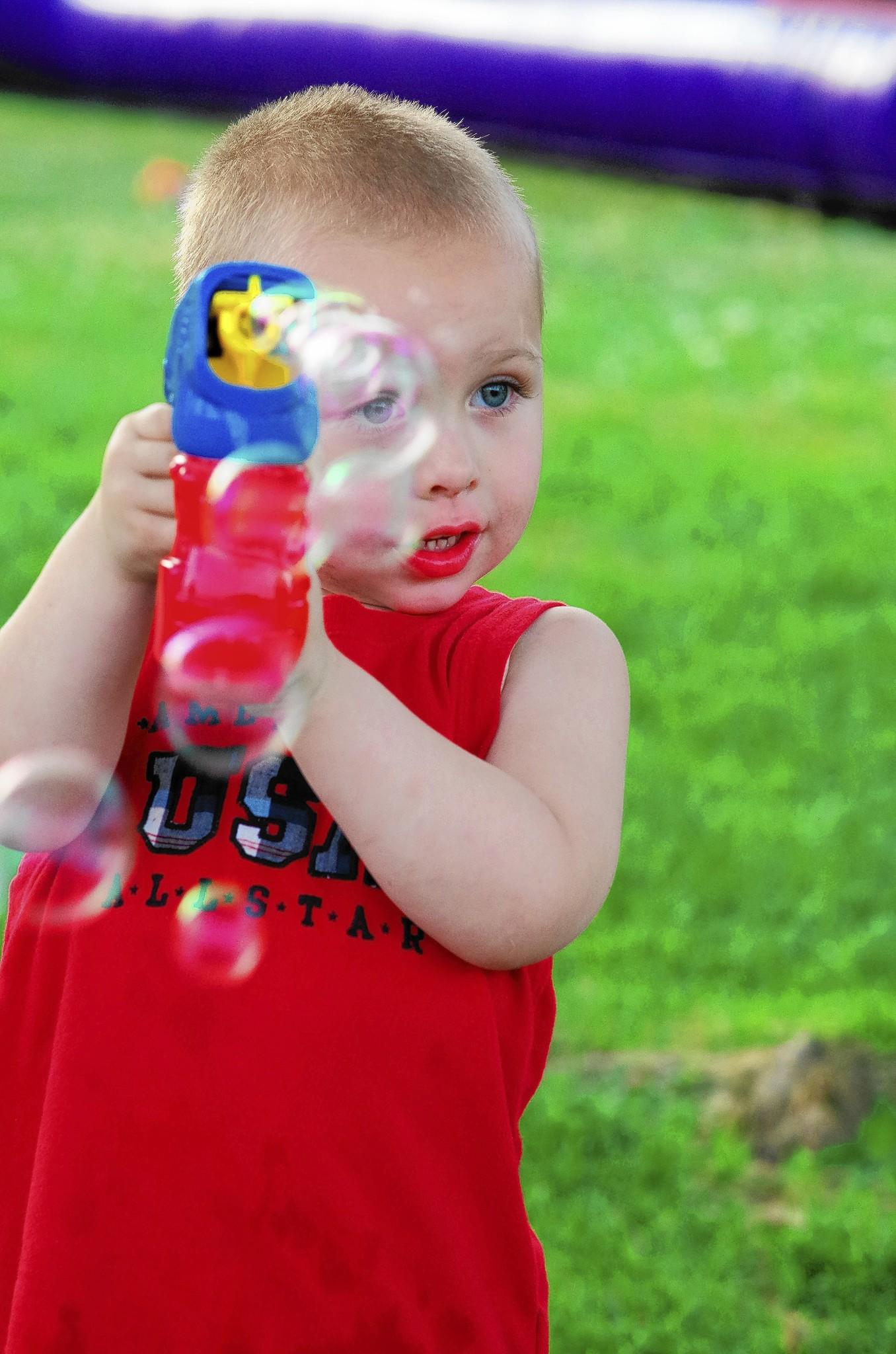 Aiden, 3, fires his bubble gun while waiting for the fireworks to begin. Photo by Steve Smith.