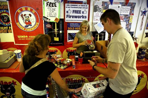 Miranda Panos, center, checks out customers Dani Ramos, left, and Jeremy Weirick at Uncle Sam's Fireworks in Hammond, Indiana. Panos, a manager at Uncle Sam Fireworks, works from 8 a.m. to midnight during the week before the Fourth of July, subsisting on Aurelio's Pizza ordered via speed-dial on the company's phone.