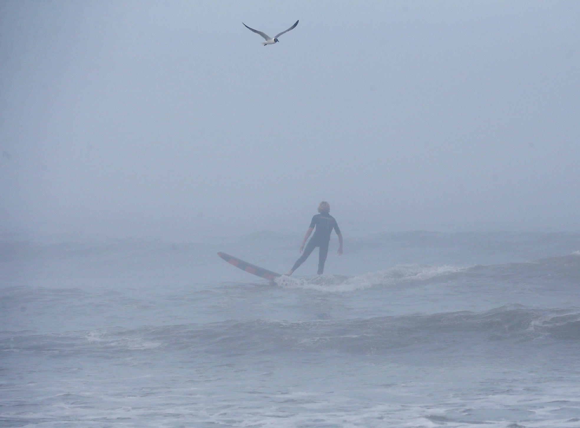 A man surfs in the fog as strong winds and heavy surf from Hurricane Arthur begin to roll in in Nags Head, North Carolina.