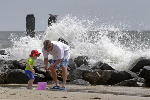 Greg McCauley inspects rocks with his two-year-old Gabriel as waves crash into rocks on the shore of Buckroe Beach Friday morning.