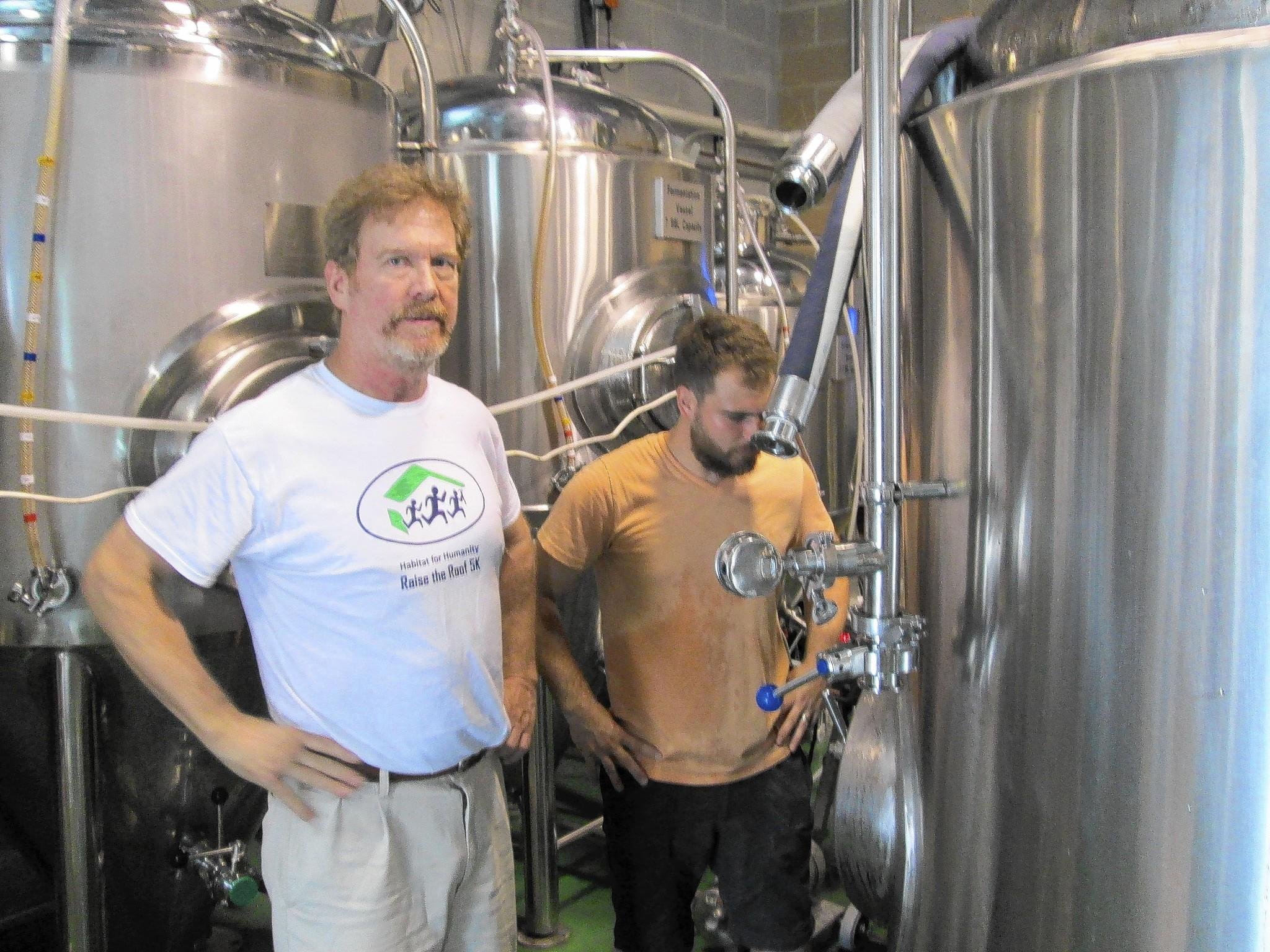Head Brewmater Doug Stoffer (left) and Assistant Brewmaster Mike Kristin(right) transfer beer into a vat.