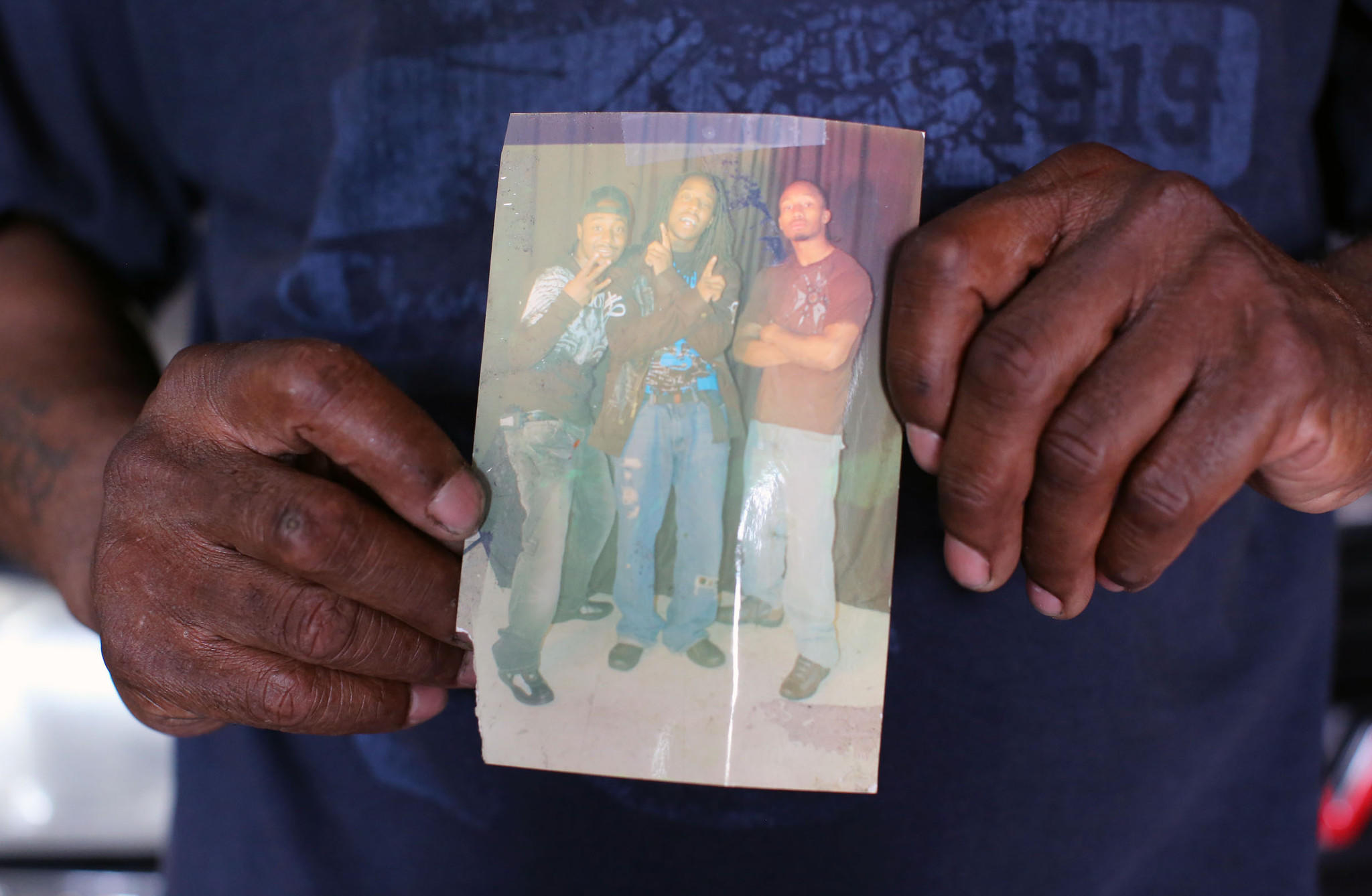 "Gordon Wilder holds a 2007 photo of his son Ramon, half-son Brandon, and their friend Brian, known as ""Speedy"" in front of Ramon's old car, a 1999 GMC Denali, in Wilder's garage on Wilkens Ave. Brandon is being charged with the murder of Wilder's son Ramon, after growing up together."
