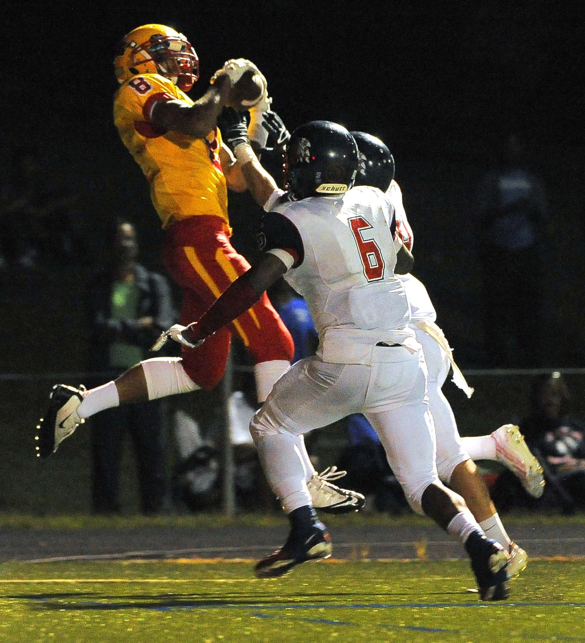 Calvert Hall's Lawrence Cager catches a pass in the end zone for a touchdown above Franklin's Taurus Bruton (6) and R.J. Mays during a game last September.
