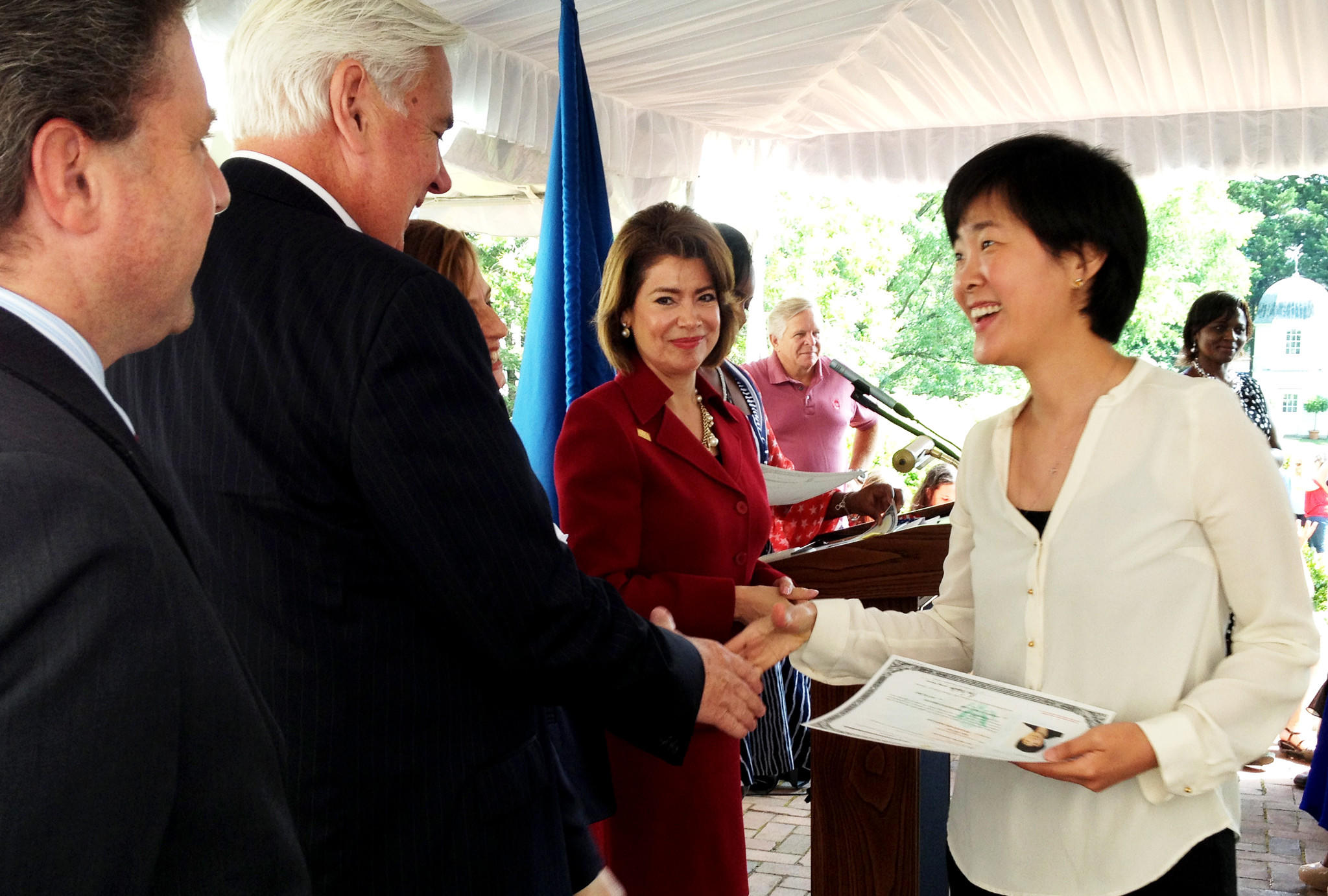 Robert C. Clark, president and CEO of Historic Annapolis, congratulates Man Yip on becoming a U.S. citizen as U.S. Small Business Administration chief Maria Contreras-Sweet looks on. Yip was one of 37 immigrants from 29 nations who were naturalized Friday during a ceremony at the William Paca House & Garden in Annapolis.