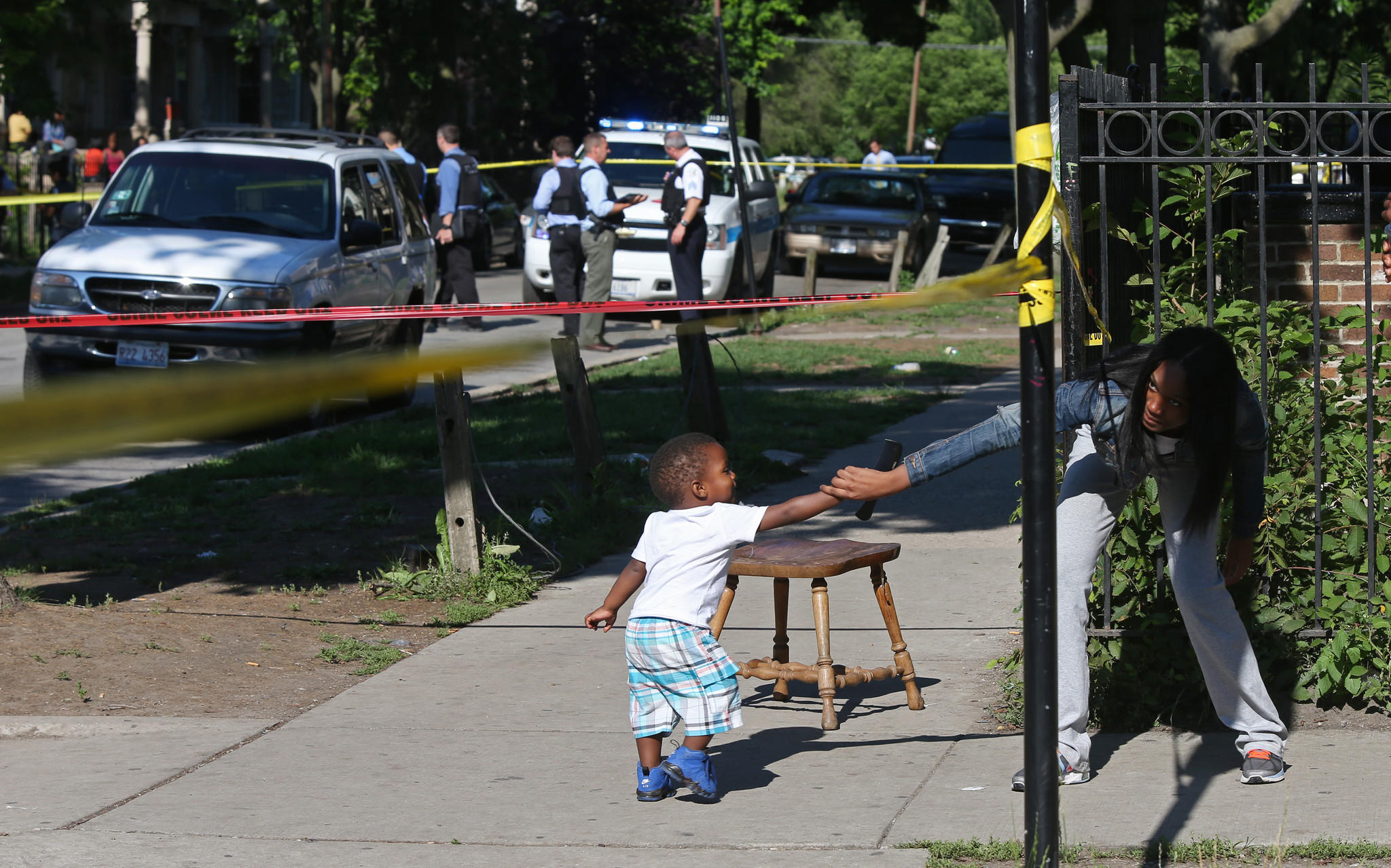 A woman grabs a child as he crosses police tape at the scene of a double-shooting in the 3800 block of West Monroe Street.