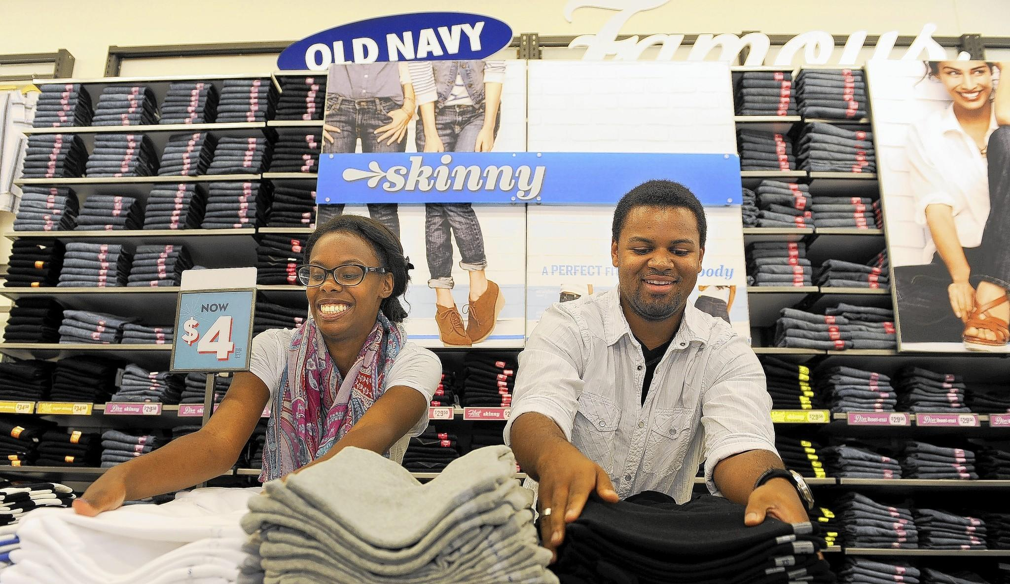 Keyerra Jeter (left) and Aaron Moon fold clothes at an Old Navy store in Gambrills. Old Navy's parent company, Gap Inc., recently raised its minimum wage to $9.