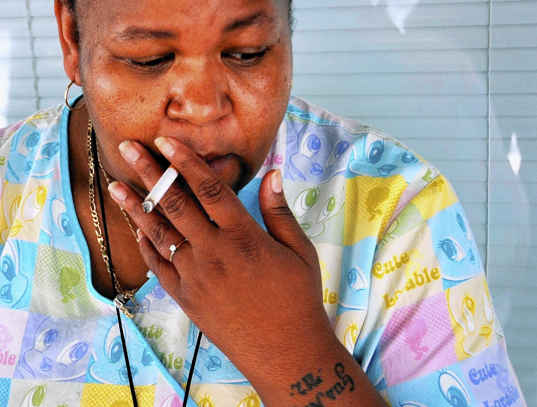 Nickia Trafton, a phlebotomist at Mercy Medical Center in Baltimore, pauses to smoke a cigarette during a break.