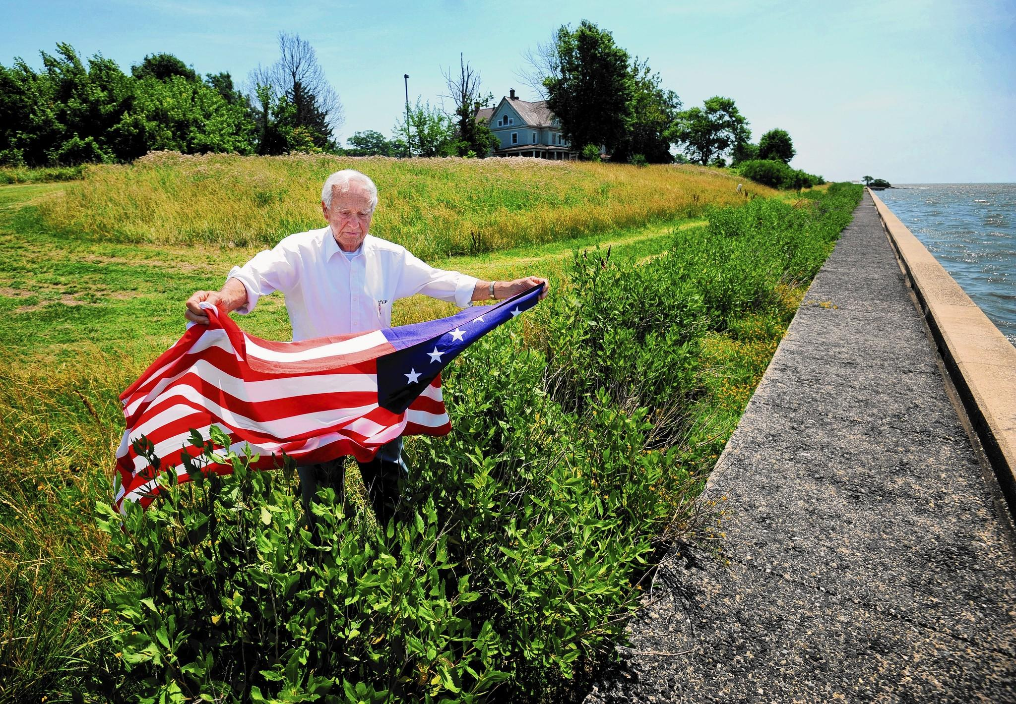 Alfred Clasing is one of the veterans that paid a deposit to a developer for a veterans' housing development on Fort Howard that never materialized. Clasing holds a 15 star American flag on Ft. Howard near the Chesapeake Bay.
