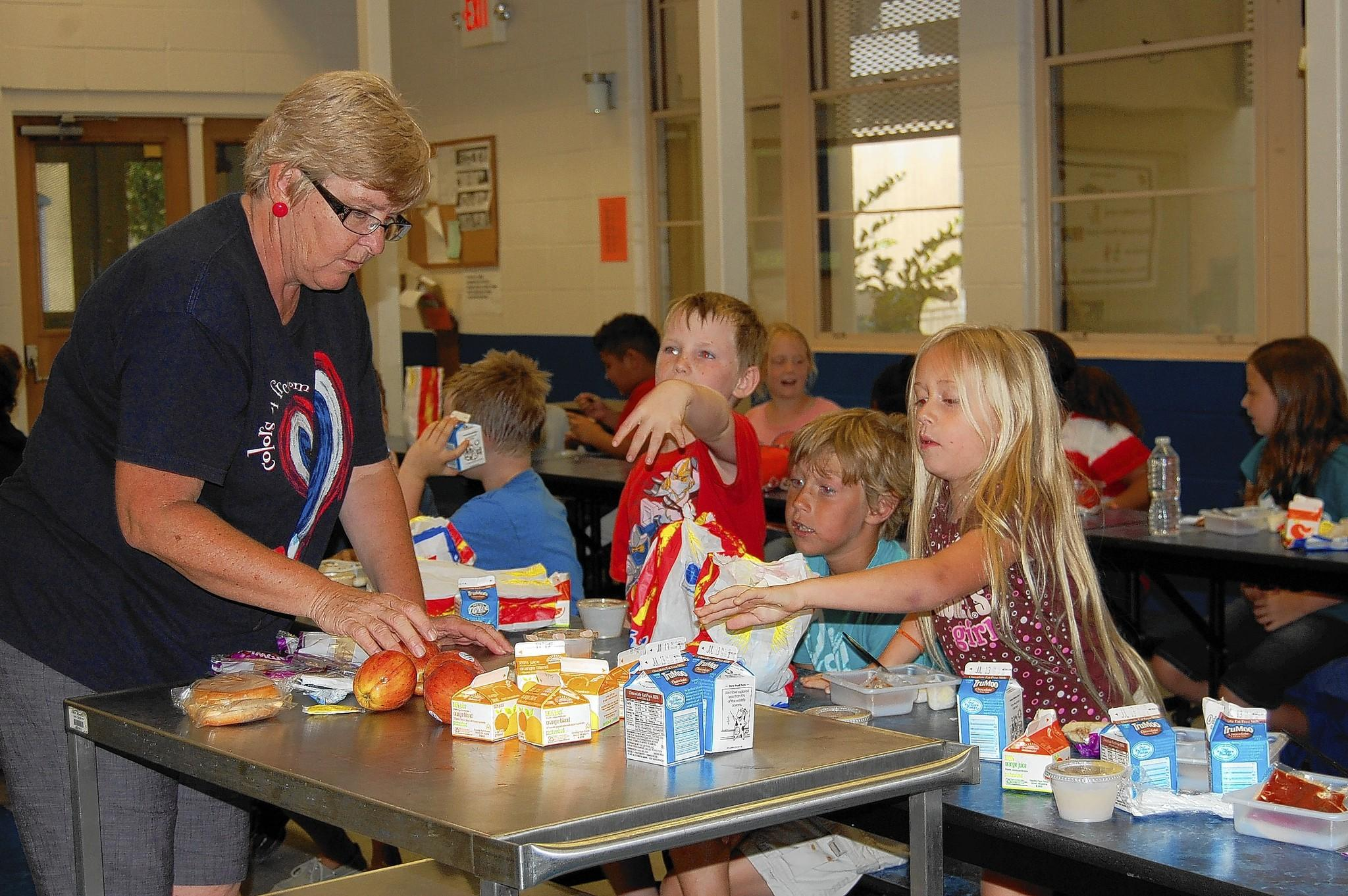 Kim Brown, left, serves free food to children at Eustis Elementary School.