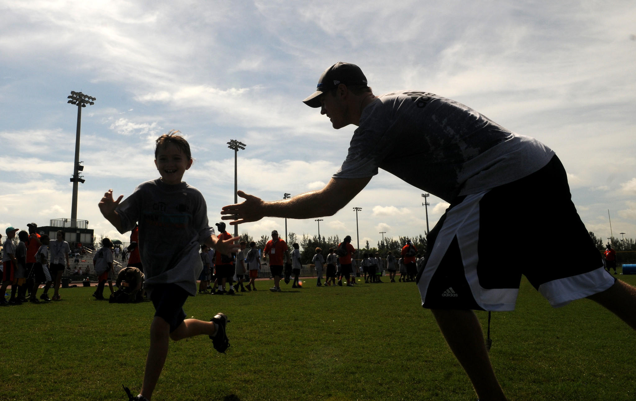 fl-tannehill-youth-camp-0708-11: (right) Miami Dolphins quarterback Ryan Tannehill high fives a camper as she crosses the finish line after a race during 2014 Citi Ryan Tannehill Football ProCamp at Flanagan High School in Pembroke Pines Tuesday. Photo by Taimy Alvarez, Sun Sentinel