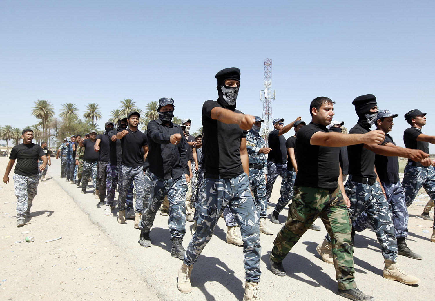 Shi'ite volunteers, who have joined the Iraqi army to fight against militants of the Islamic State, formerly known as the Islamic State of Iraq and the Levant, march during training in Baghdad on July 9.