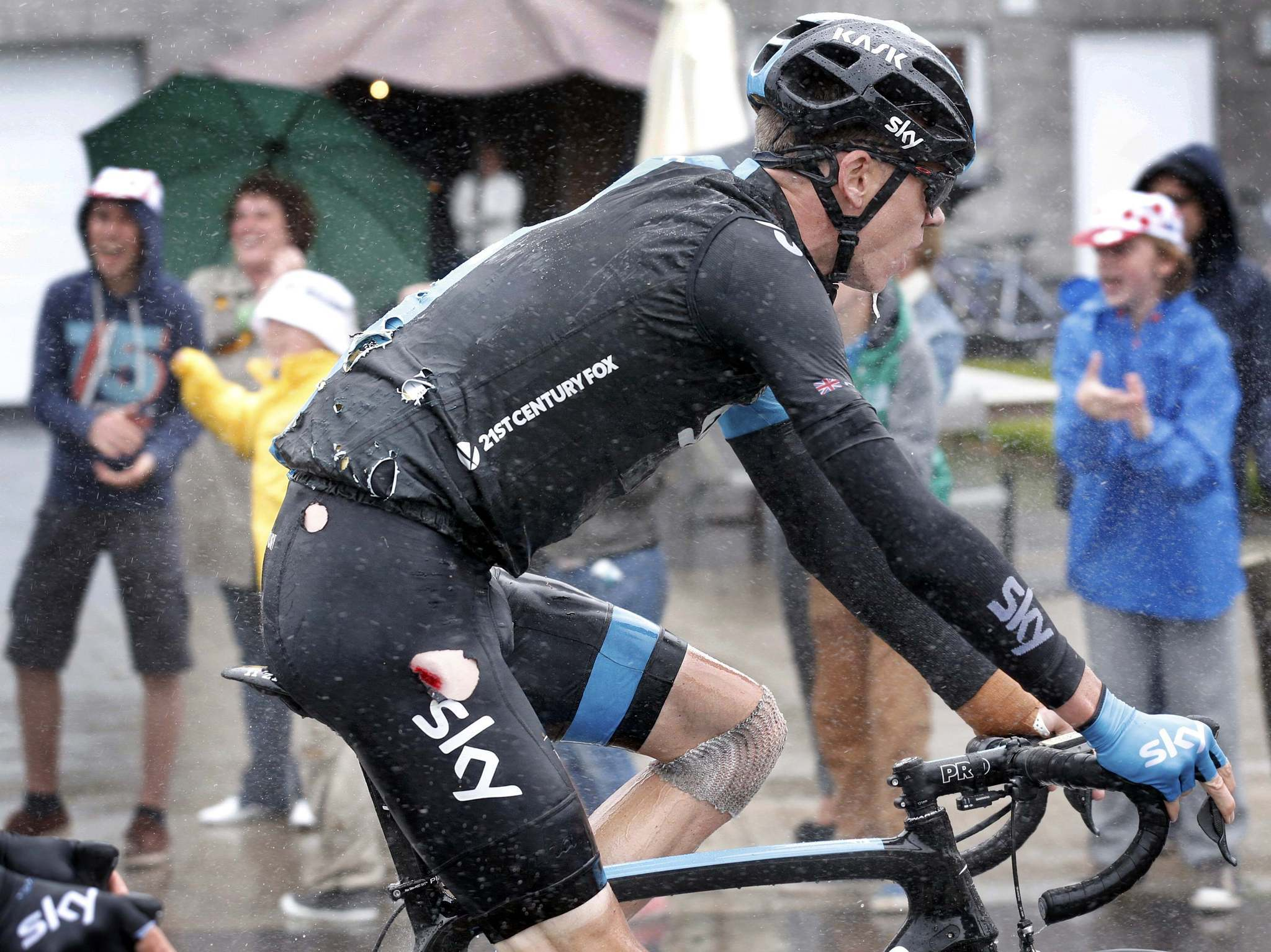 Christopher Froome of Britain rides in his torn cycling costume after falling in the 5th stage of the Tour de France.