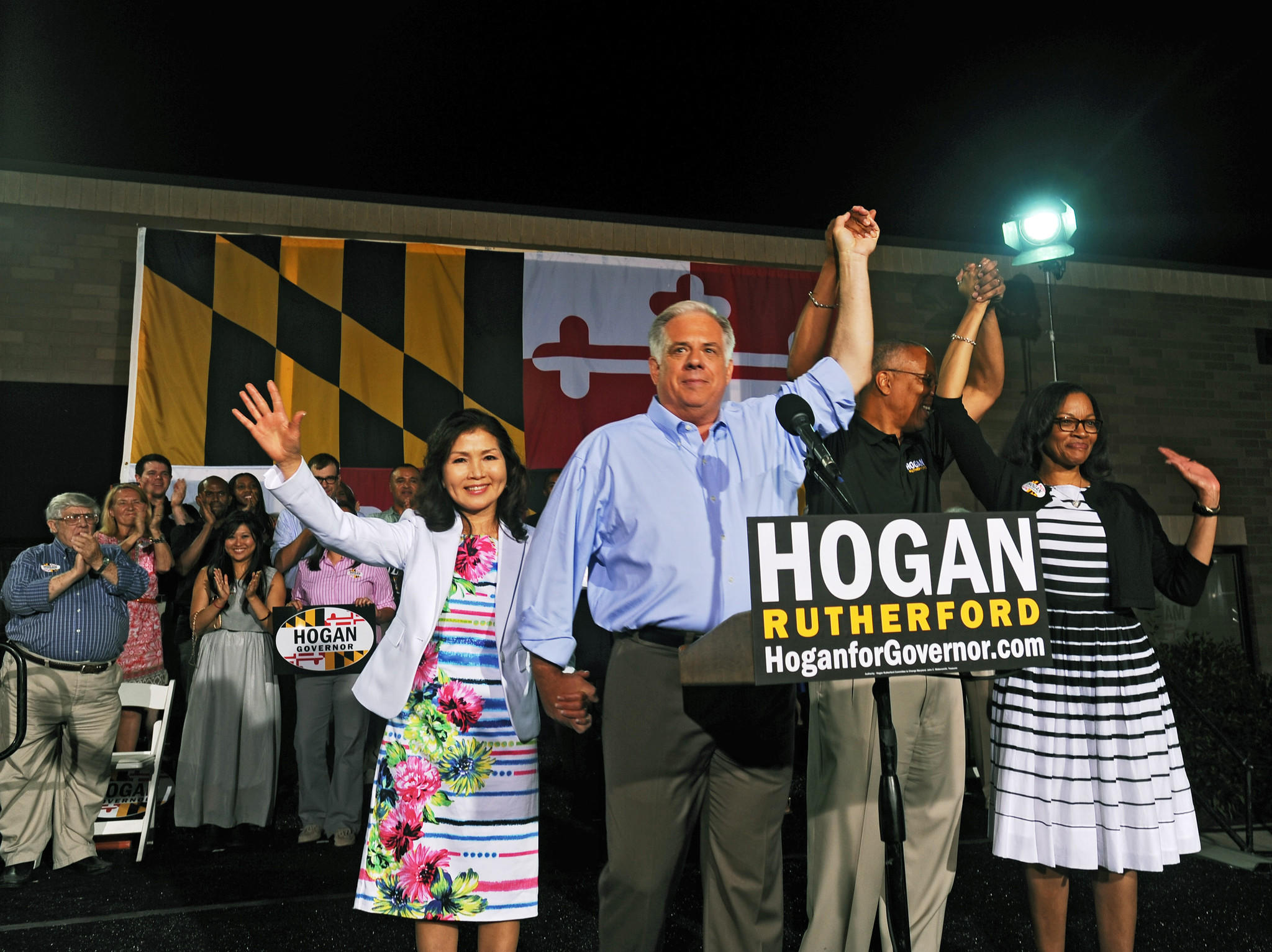 Republican gubernatorial candidate Larry Hogan, second left, and running mate Boyd Rutherford, third from left, and their respective spouses, Yumi Hogan, left, and Monica Rutherford, right, wave to supporters after declaring their primary victory outside their campaign headquarters.
