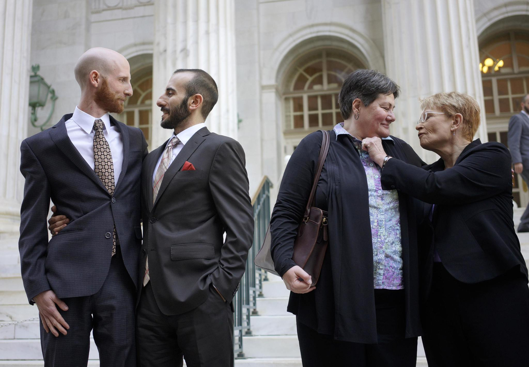 Plaintiffs Derek Kitchen (L-R) and Moudi Sbeity and Kate Call and Karen Archer talk outside the courthouse after a federal appeals court heard oral arguments on a Utah state law forbidding same sex marriage in Denver in an April 10, 2014.