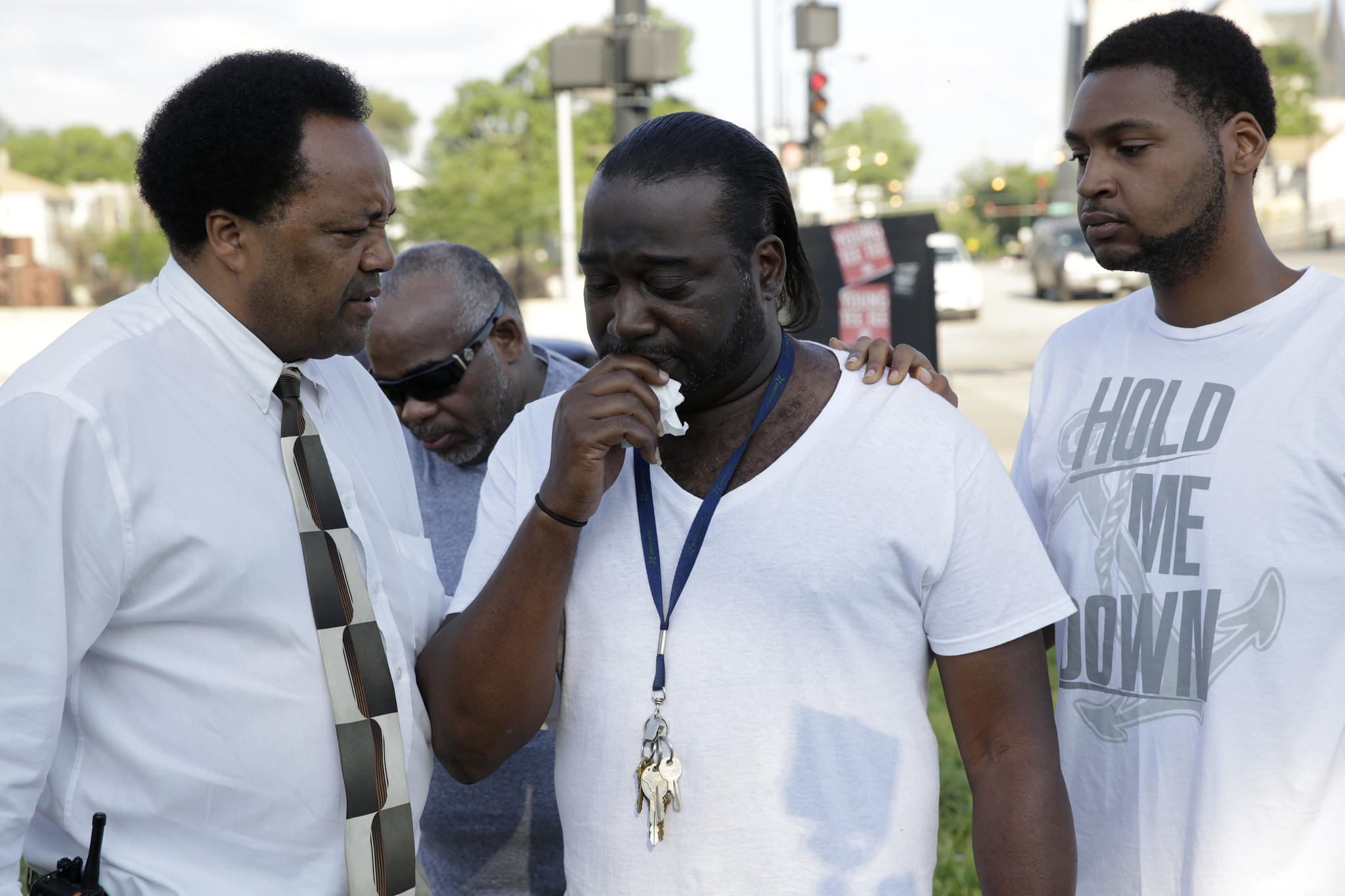 Pierre Curry, Sr., center, is consoled by community activist Andrew Holmes, left, and his cousin Eric Willis, 19, right, on 59th Street and the Dan Ryan Expressway after his pregnant 25-year-old daughter Jasmine Curry was shot and killed on the expressway. Michael Tercha/Chicago Tribune)
