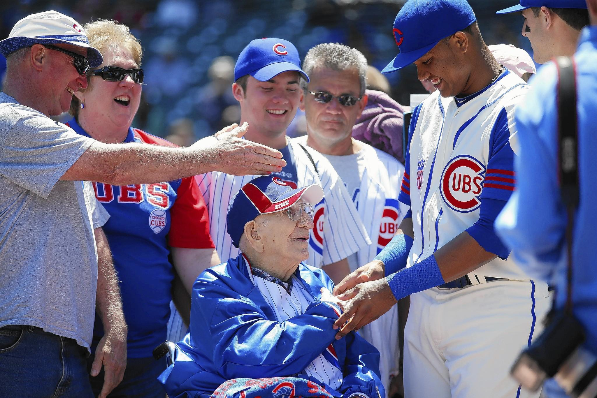 Louis Reinhart, a retired farmer from Metamora, is greeted by Chicago Cubs shortstop Starlin Castro (13), right, during pre-game activities prior to a game between the Chicago Cubs and Miami Marlins at Wrigley Field.