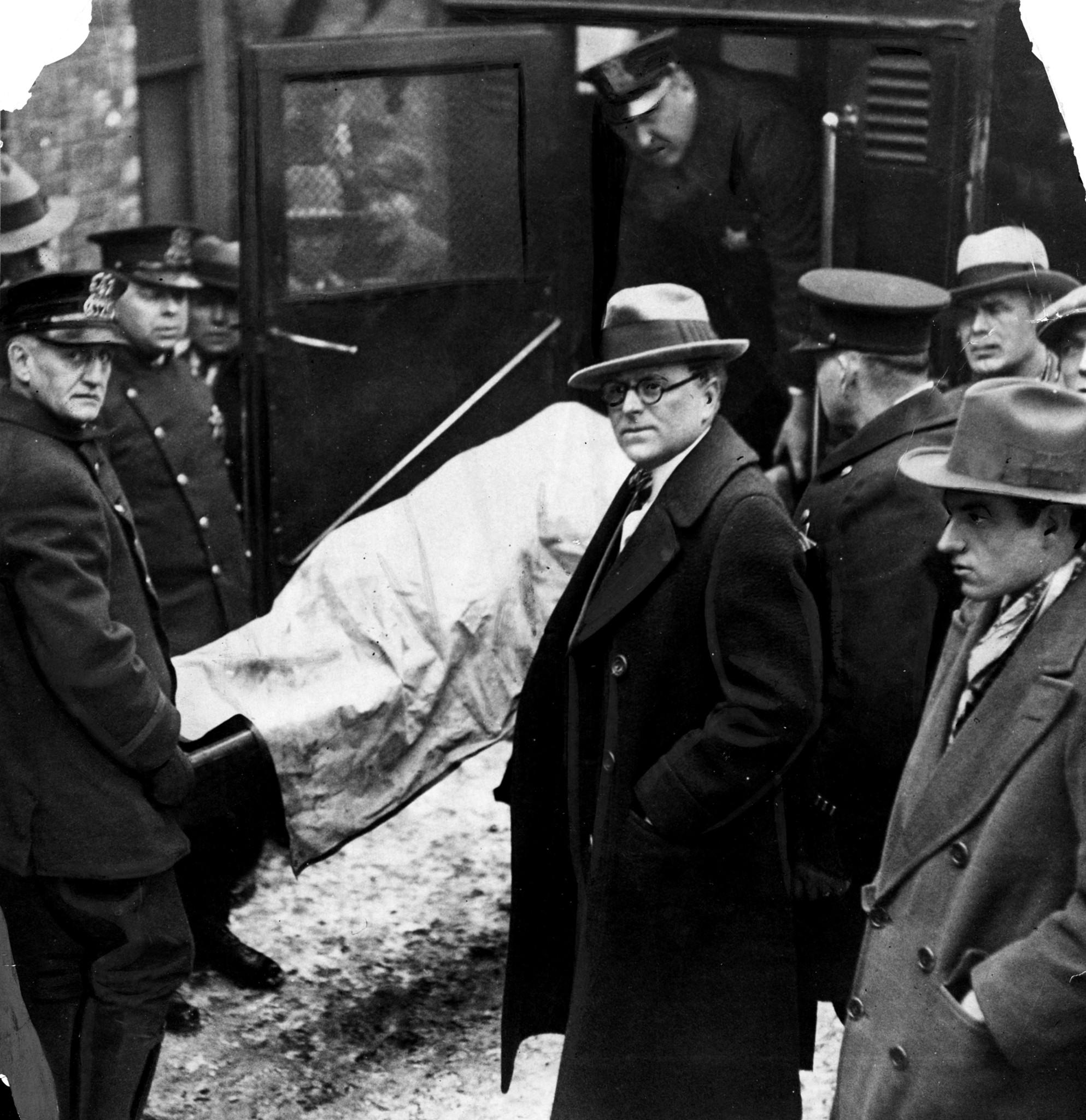 The body of one of the seven victims is placed in an ambulance with Coroner Herman M. Bundesen, center, in attendance at 2122 N. Clark Street on Feb. 14, 1929.