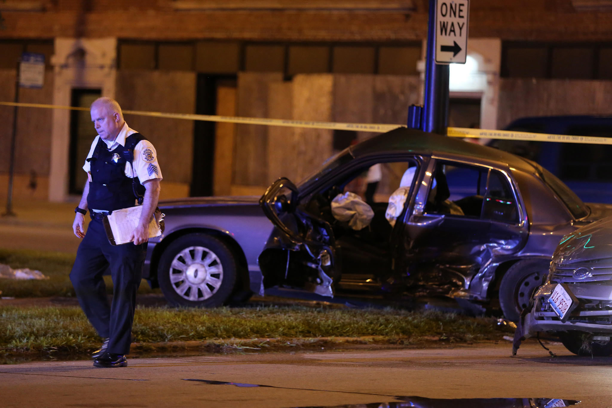 A police officer walks past the wreckage of an unmarked police car after it was involved in a collision with a sedan at the intersection of East Garfield Boulevard and South Indiana Avenue in Chicago.
