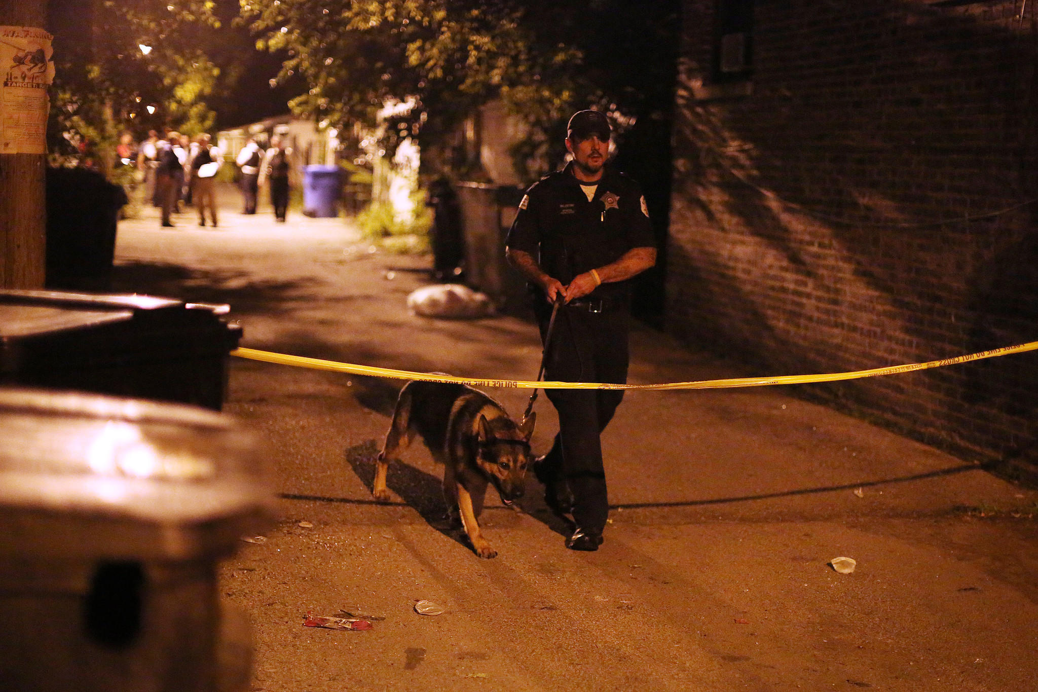 A canine officer and his dog cross under police tape at the scene where officers exchanged gunfire with a man near the intersection of West 64th Street and South Campbell Avenue in Chicago.