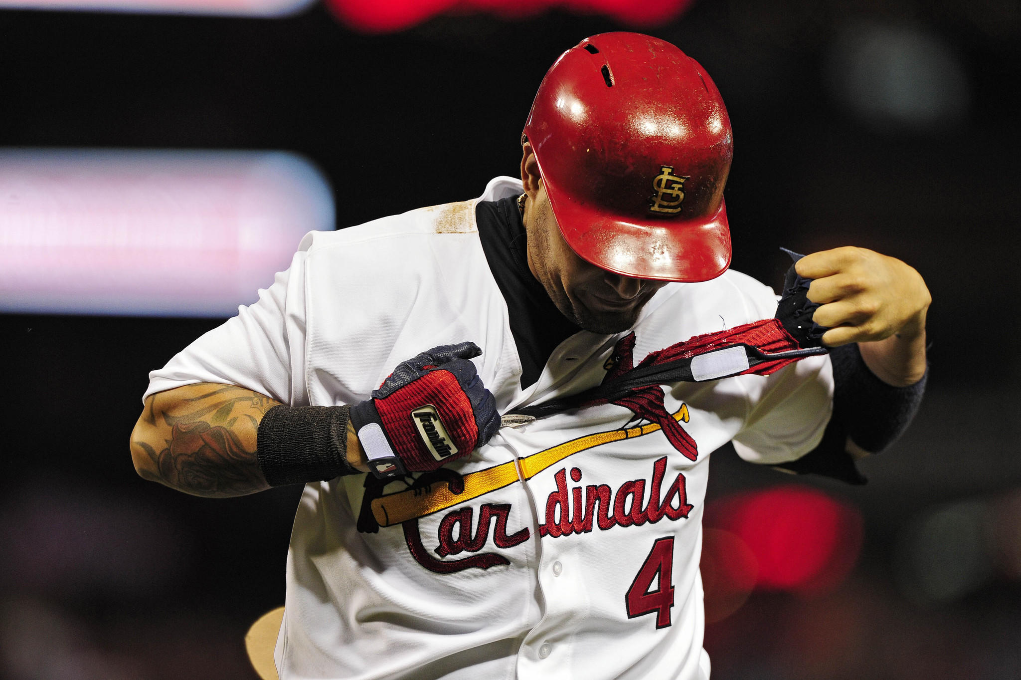 St. Louis Cardinals catcher Yadier Molina tears off his batting gloves after flying out.