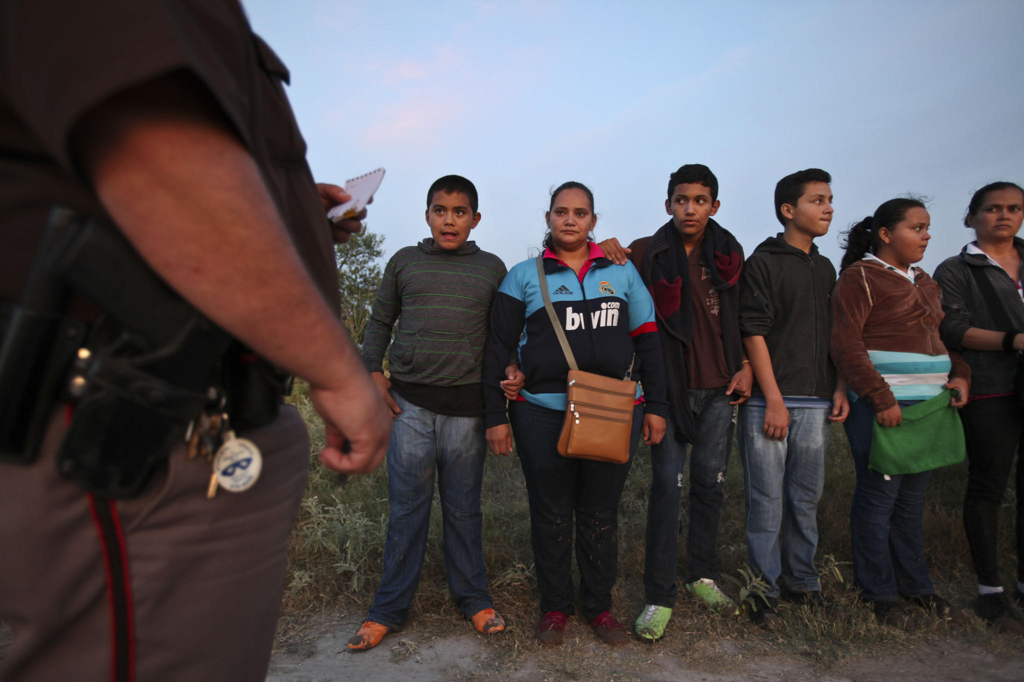 MCALLEN, TX-JUNE 12, 2014: Deputy Ruben Salinas, left, of the Hidlago County Constable Department, questions a group of 16 Guatemalans after they crossed the Rio Grande near Anzalduas Park outside McAllen, Texas.
