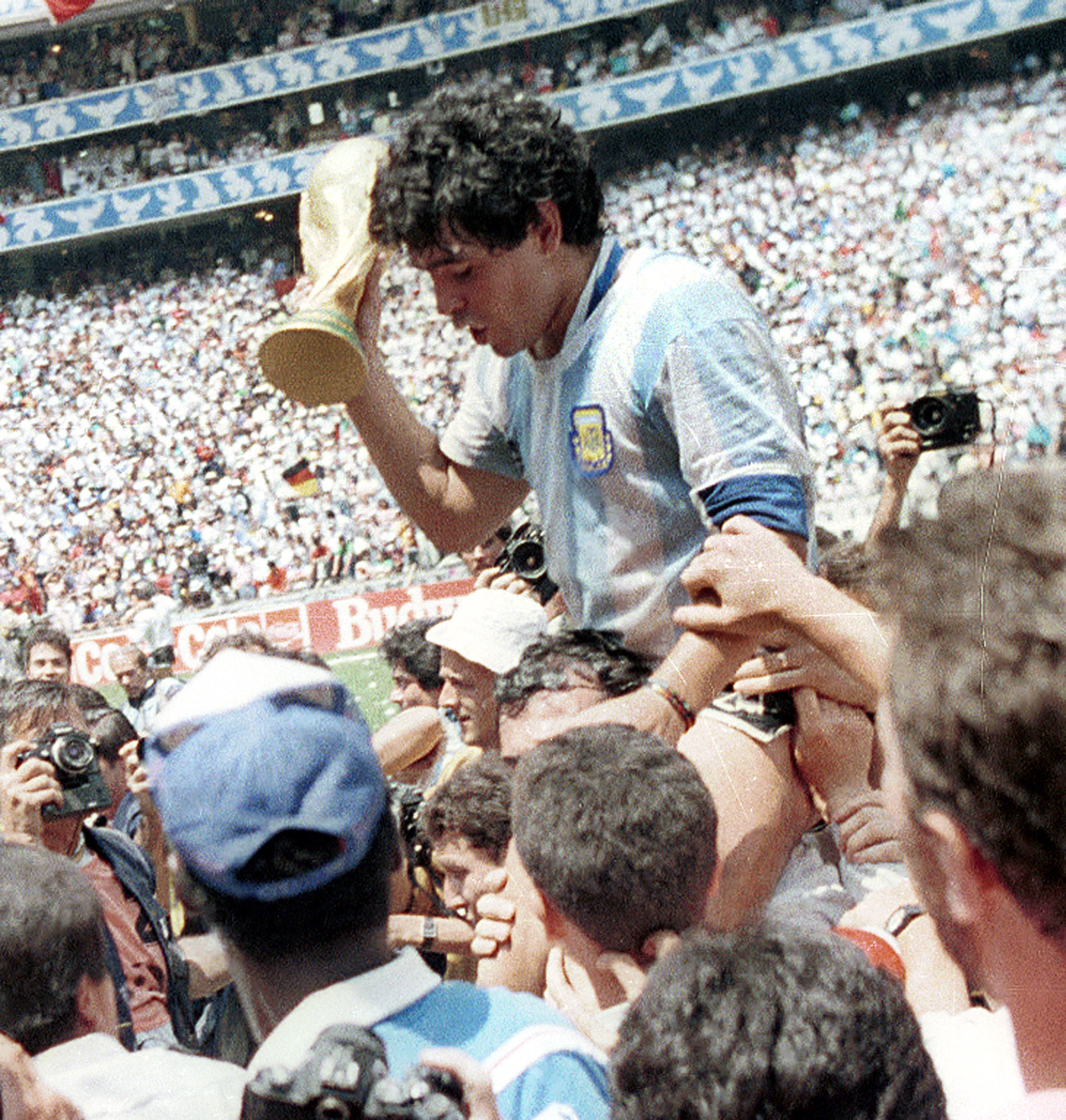 Diego Maradona holds the World Cup trophy at the Azteca stadium in Mexico City.