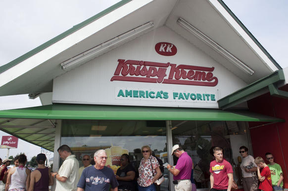 Customers line up outside the Krispy Kreme on Mercury Boulevard in Hampton to take advantage of a sale in honor of the company's 77th birthday on Friday.