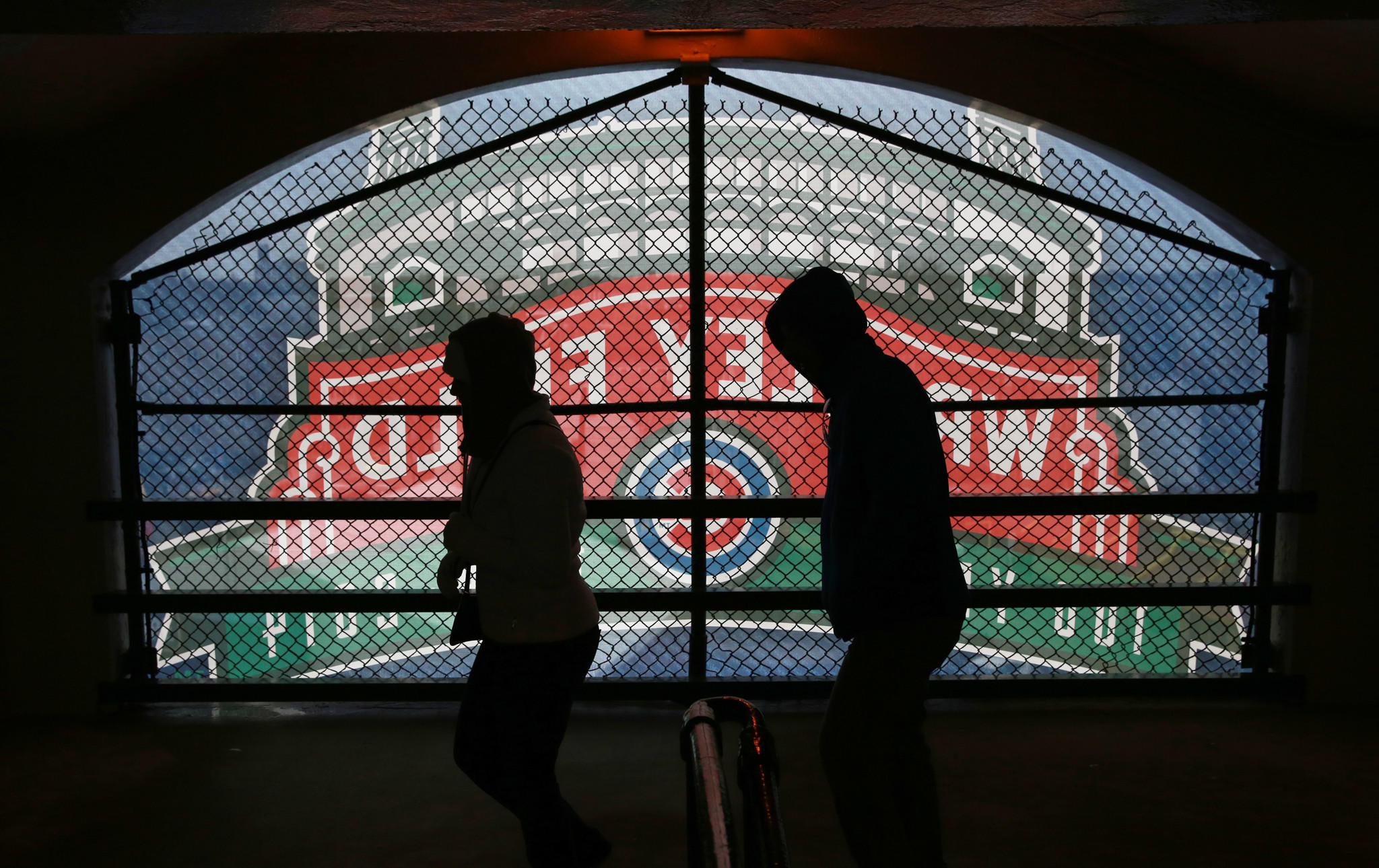 Two fans walk past an awning sign before the Chicago Cubs home opener against the Phillies at Wrigley Field on April 4. (John J. Kim/Chicago Tribune)