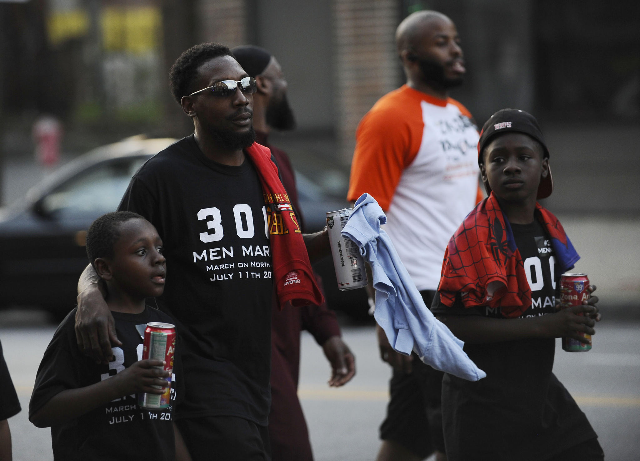From left, Zachary Gaines IV, 8, marches with his father, Zachary Gaines and brother Isaiah, 10, all of Baltimore, during the 300 Men March.