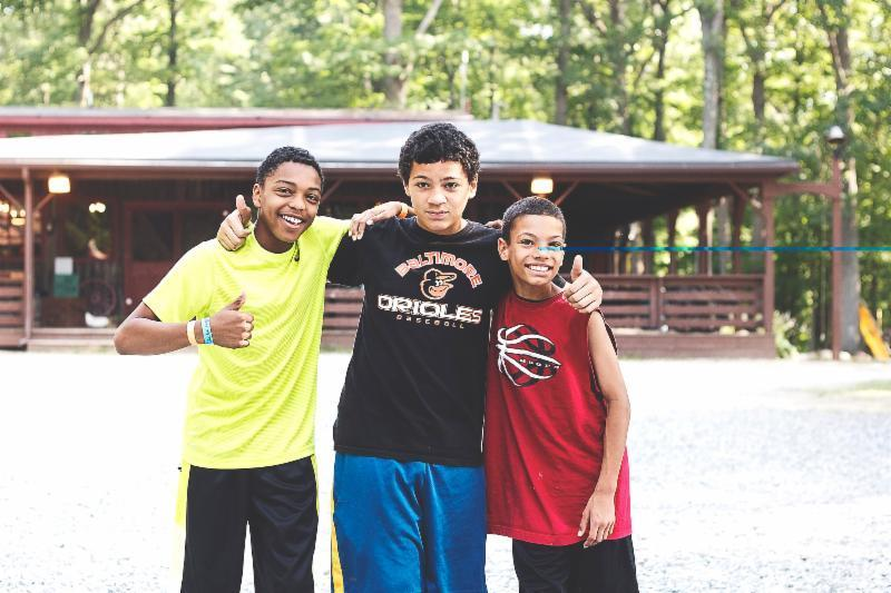 Justin Nicholas Diggs (left) is pictured with two of his fellow campers.