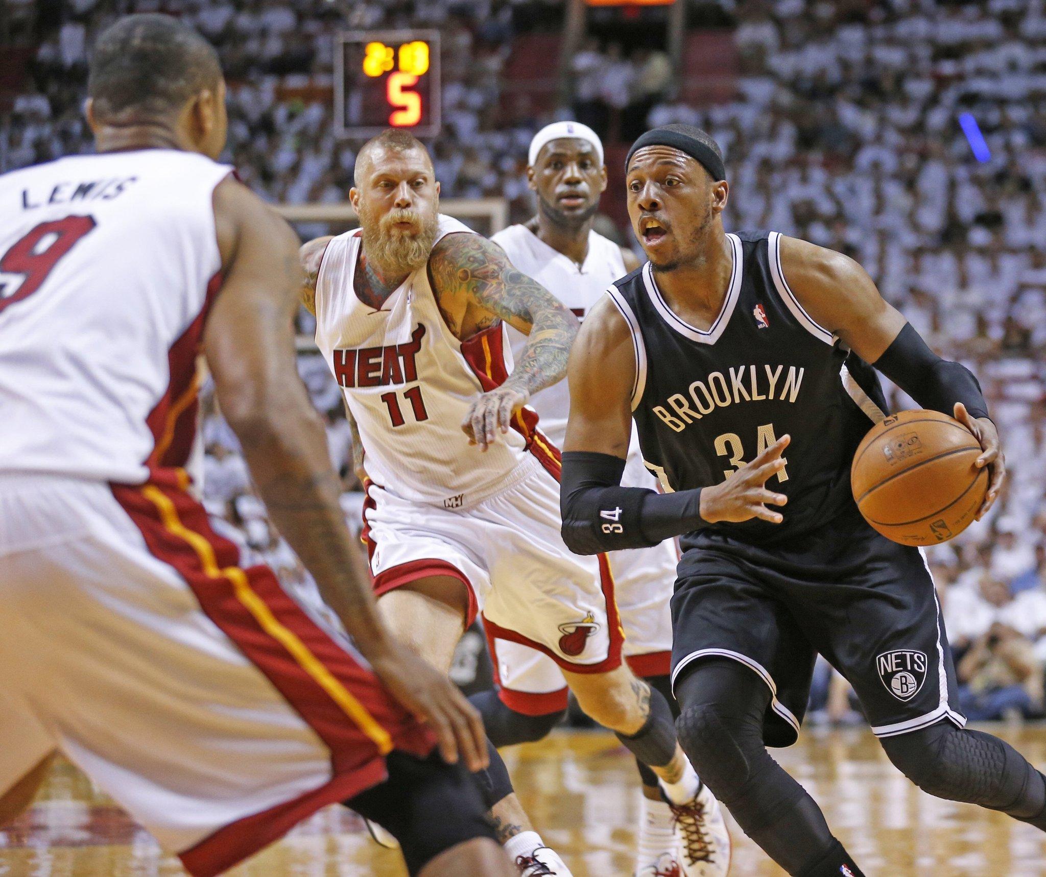 Brooklyn Nets' Paul Pierce looks to pass around Miami Heat defender Rashard Lewis.