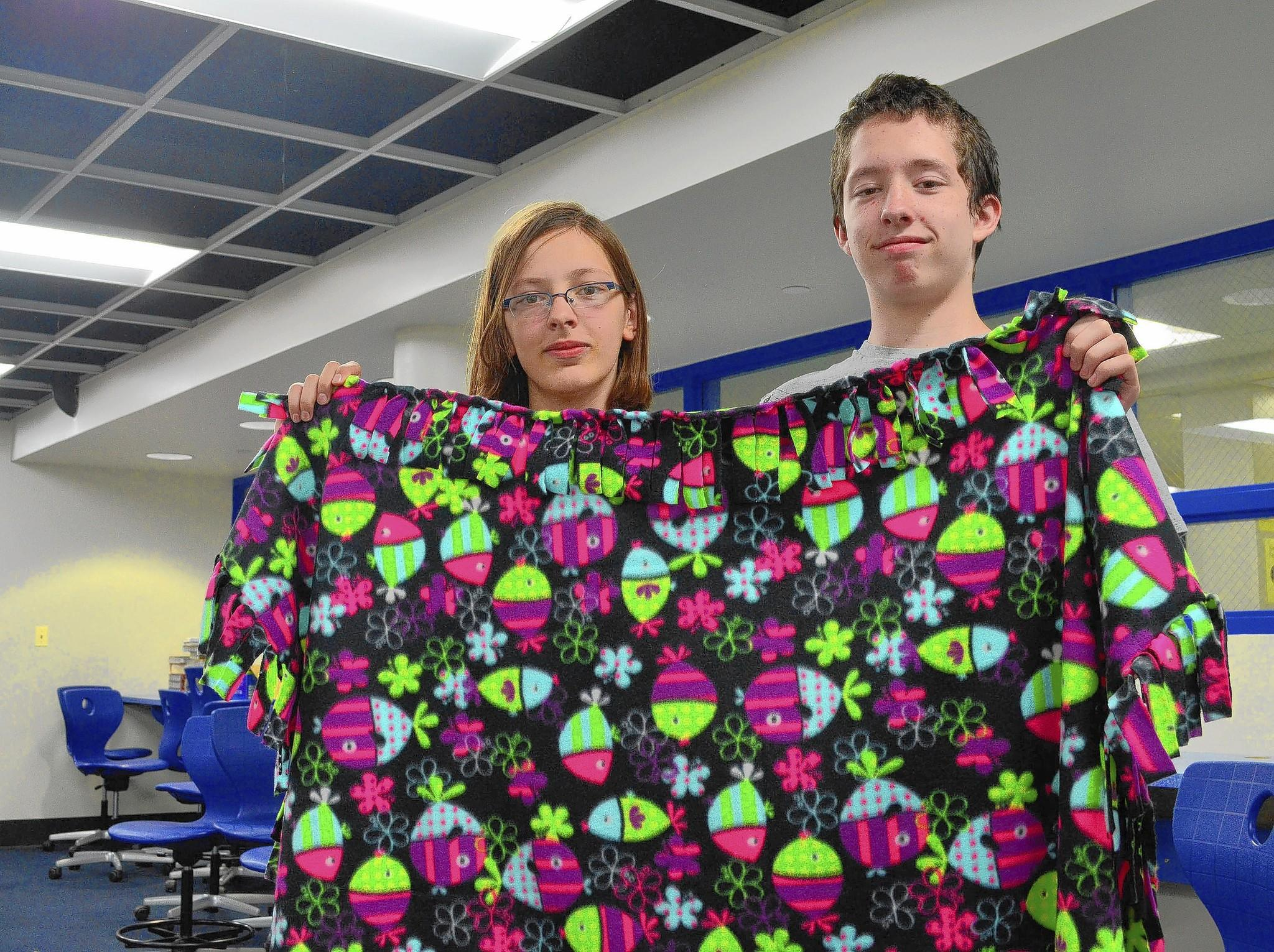 Veronica Kleinschmidt and Nick Heidrich, both 7th-graders, show a completed blanket.