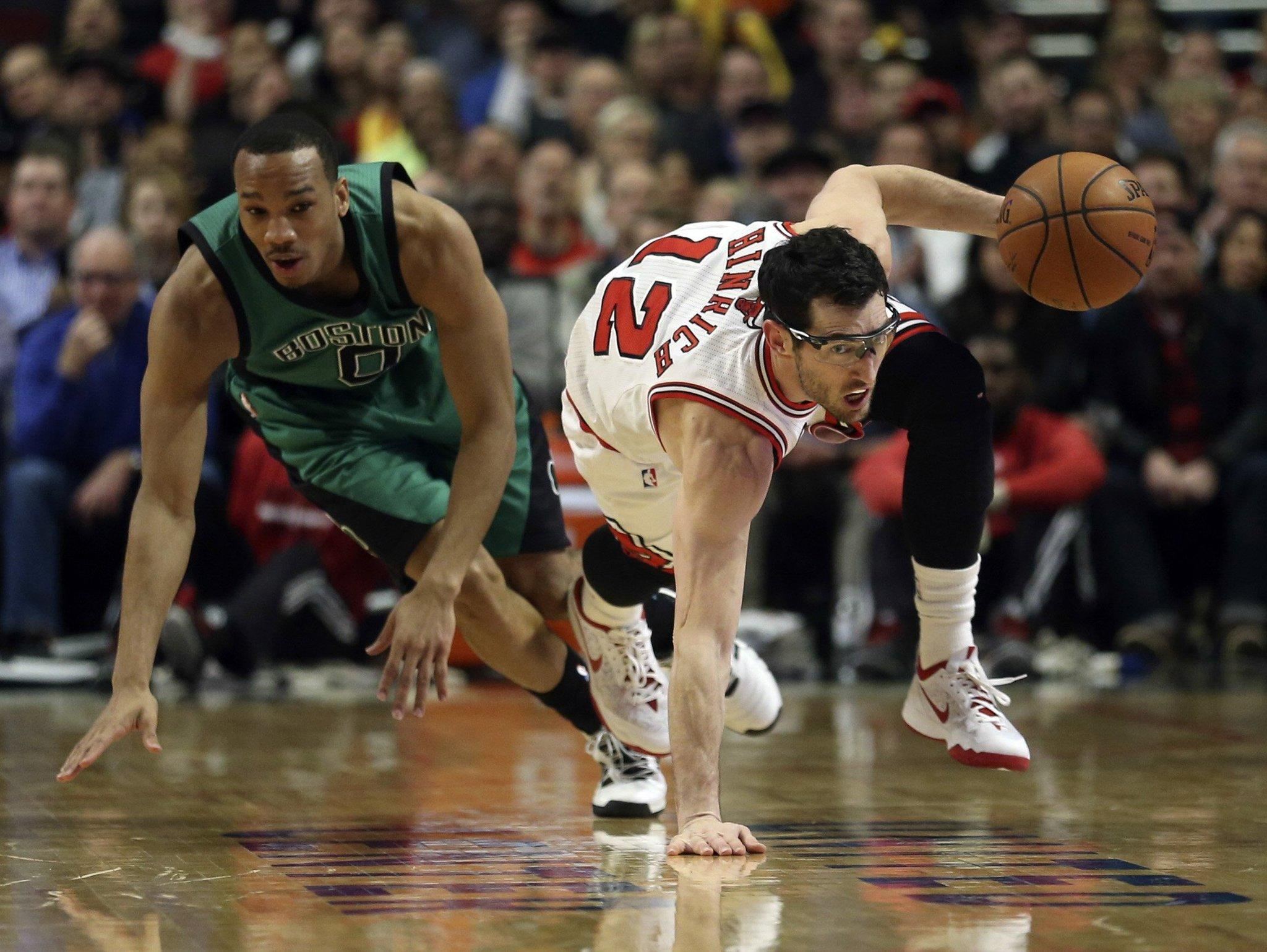 Kirk Hinrich scoops up a loose ball in front of the Celtics' Avery Bradley during the first half at the United Center.