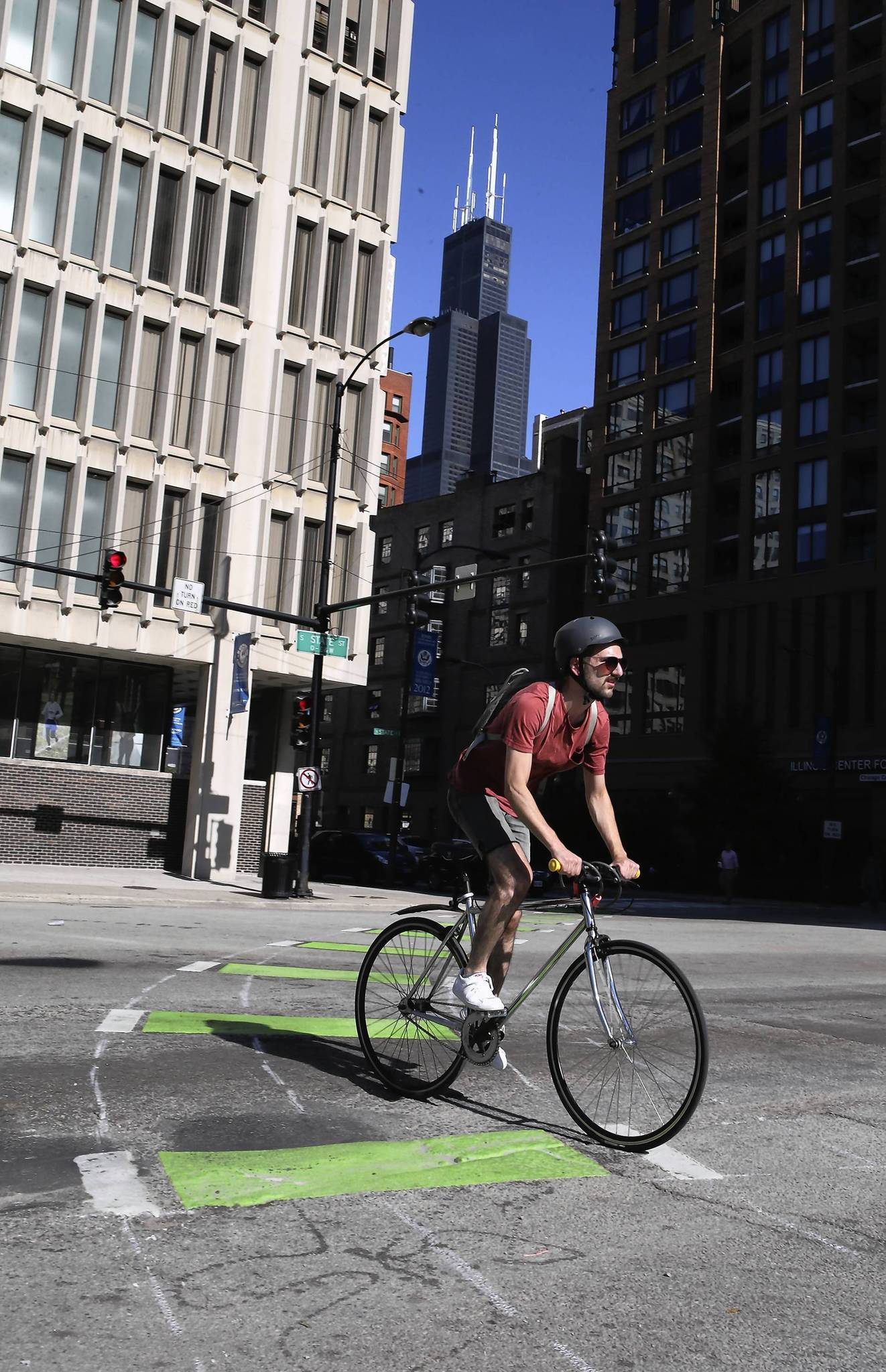 A bicyclist navigates the new curved bike lanes painted on the Harrison and State street intersections in Chicago.