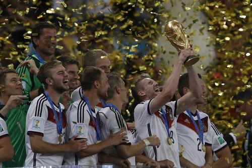 Germany forward Andre Schuerrle, center, holds the trophy as he celebrates with teammates after they beat Argentina for the FIFA World Cup at Maracana Stadium in Rio de Janeiro.