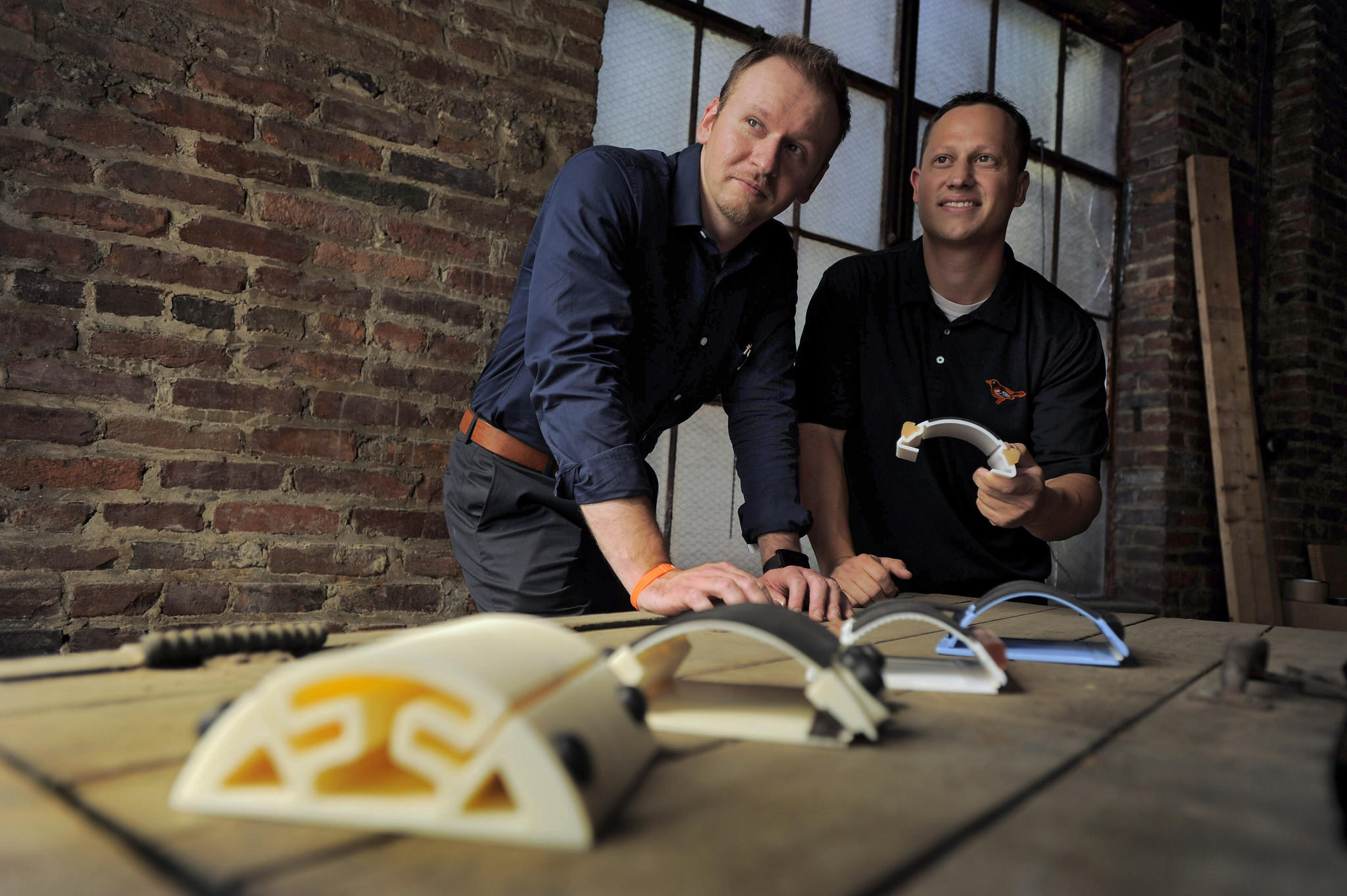 Gene Shirokobrod (left) and Corey Fleischer, who holds a 3D-printed prototype of the Kickstarter-funded model of the Arc at the Foundery.