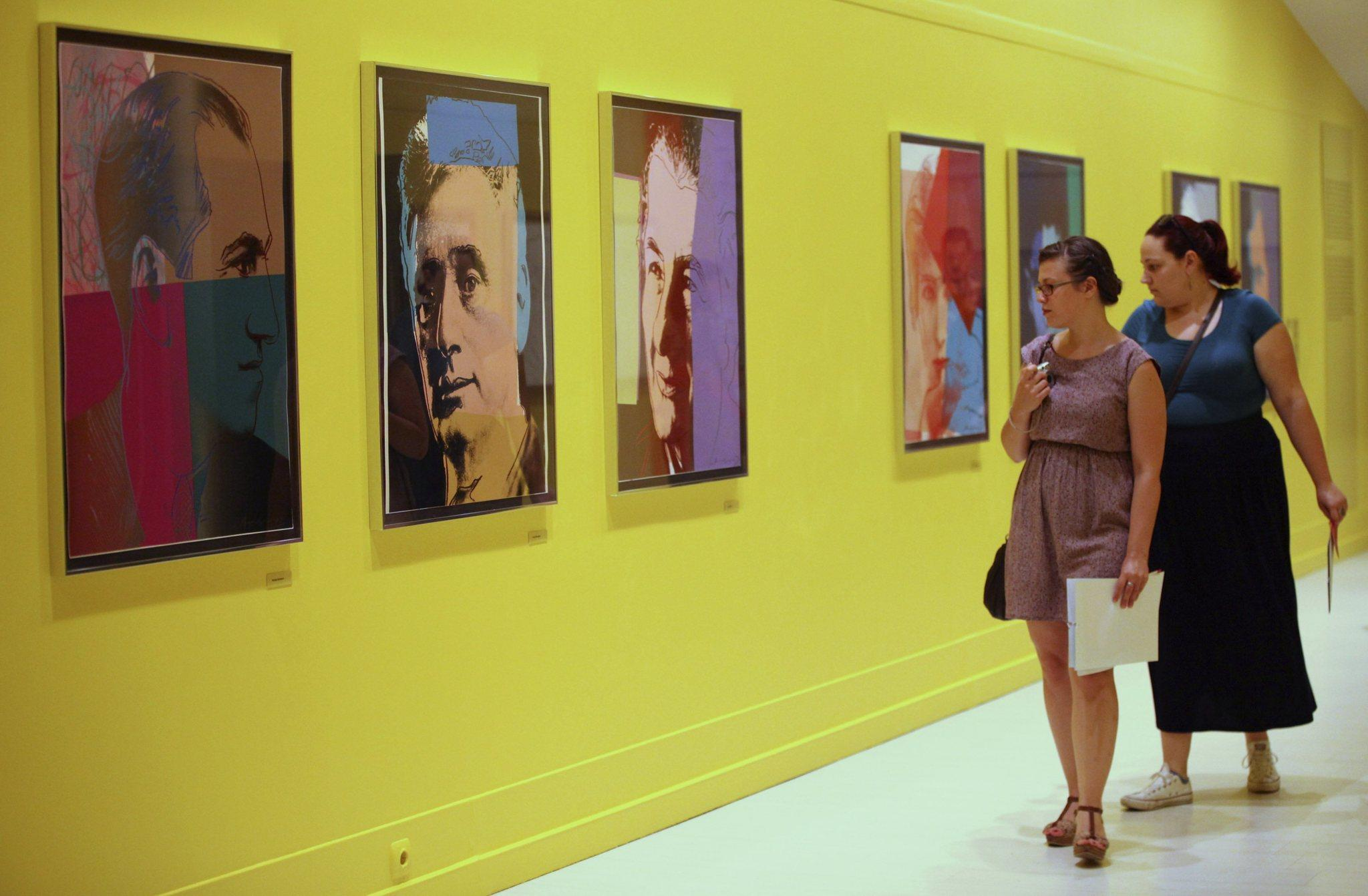 Visitors look at artworks at Pera Museum in Istanbul June 10, 2014. A show of Andy Warhol's most evocative and familiar images at Istanbul's Pera Museum portrays the pop art great in a very personal light.