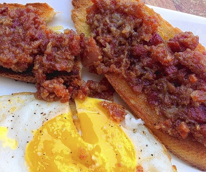 Two toasted baguette slices are spread with bacon jam and served with a sunny-side-up egg.