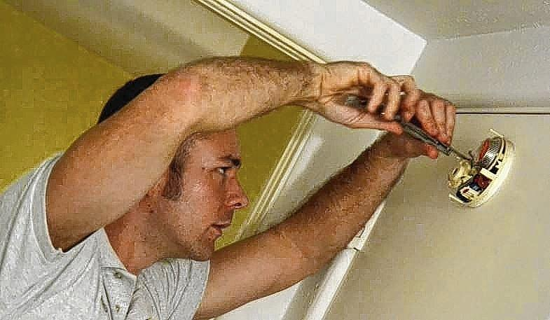 Mount Dora firefighter Casey Forney installs a smoke detector.