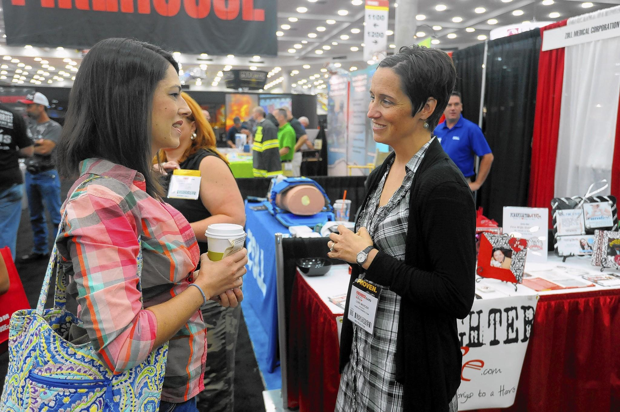 Left to right, Becky Fleitz, of Roanoke, Va., speaks with Lori Mercer, founder of Firefighterwife.com, an online community for the wives, fiancees and girlfriends of firefighters, at the Firehouse Expo in the Baltimore Convention Center.