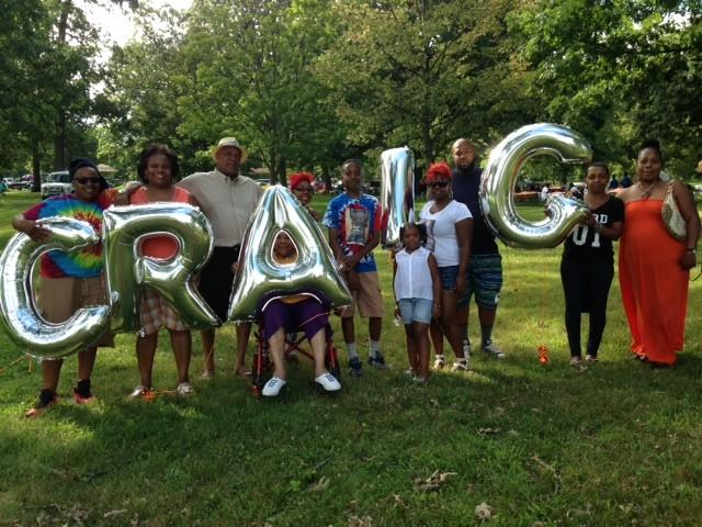 Loved ones pose near balloons spelling Craig at a cookout held in memory of slain bus driver Craig Ray Jr.
