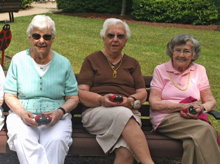 Cedar Mountain Commons residents, from left, Betty Duncan, Mary Kunz and Gerri Patti display the ladybug decorations they crafted before they were placed in the rear courtyard garden.